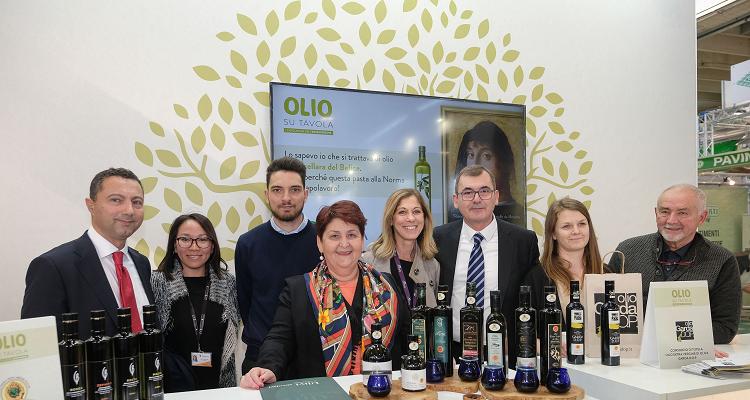 La ministra Bellanova e il suo entourage di fronte a delle bottiglie di olio